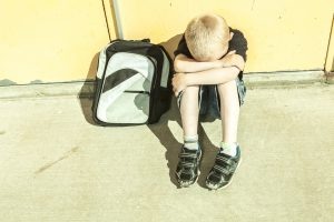 An upset child sits on concrete with his head in his hands